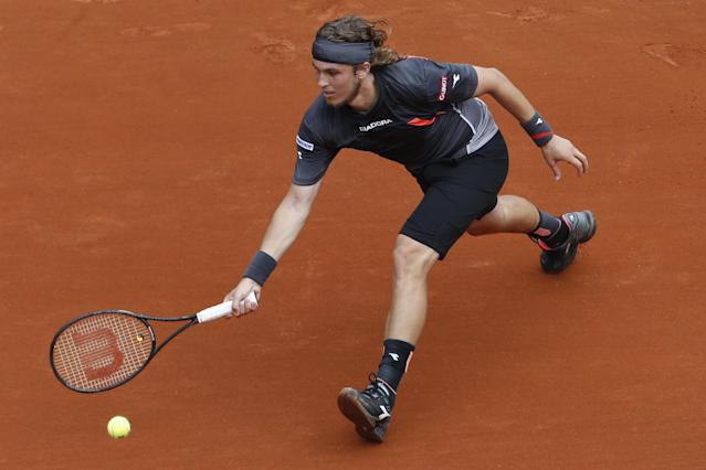 Slovakia's Lukas Lacko returns the ball during the first round match of the French Open tennis tournament against Switzerland's Roger Federer at the Roland Garros stadium, in Paris, France, Sunday, May 25, 2014. (AP Photo/Darko Vojinovic)