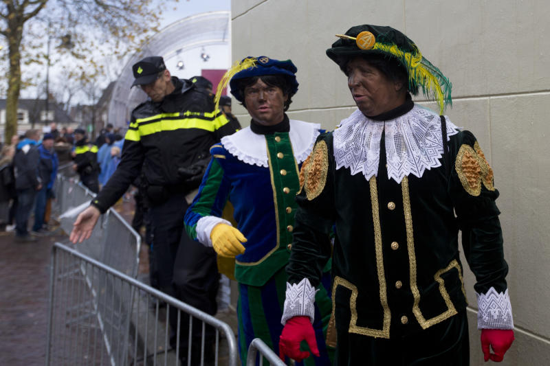 FILE - In this Nov. 18, 2017, file photo, Black Petes and police officers leave after the arrival of Sinterklaas, or Saint Nicholas in Dokkum, northern Netherlands. As some of Virginia's white political leaders grapple with long-delayed fallout from having worn blackface years ago, others who once donned blackface have been re-examining old memories of the behavior. (AP Photo/Peter Dejong, File)