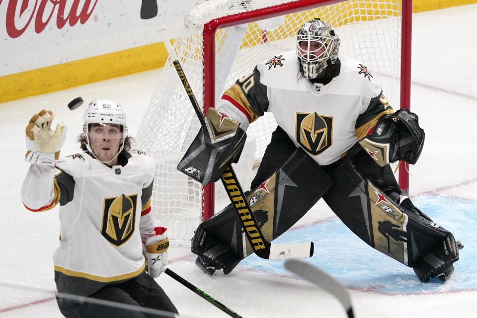 Vegas Golden Knights defenseman Dylan Coghlan, left knocks the puck out of the air as goaltender Robin Lehner watches during the third period of an NHL hockey game against the Los Angeles Kings Monday, April 12, 2021, in Los Angeles. (AP Photo/Mark J. Terrill)