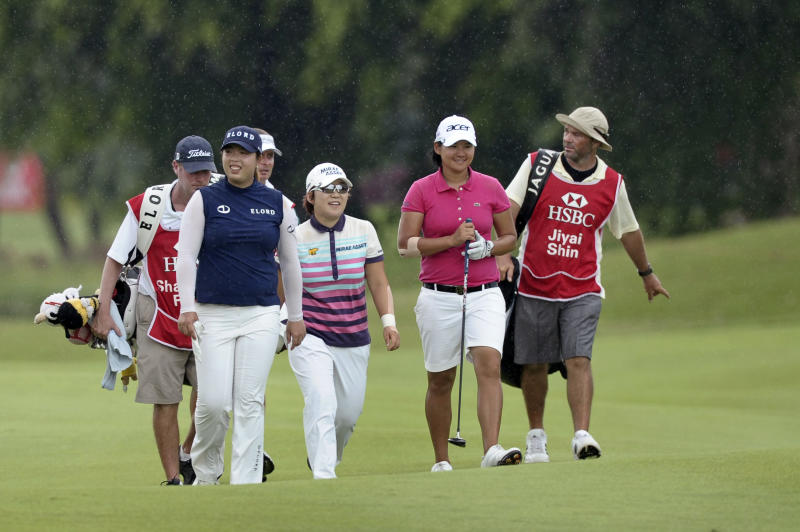 China's Shanshan Feng, second left, Shin Jiyai of South Korea, center, and Yani Tseng of Taiwan, second right, walk on the 18th fairway in the rain during the final round of the HSBC Women's Champions golf tournament Sunday, Feb. 26, 2012 in Singapore. (AP Photo/Joseph Nair)