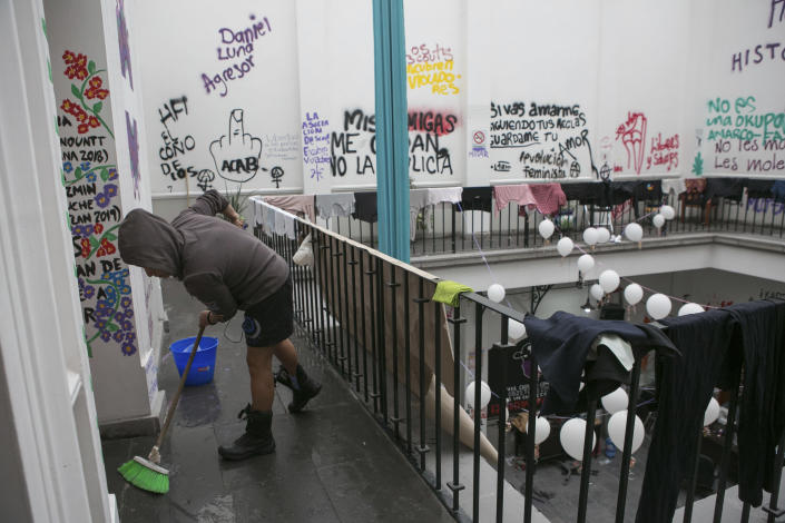 A women's rights activist cleans at the offices of the Mexican Human Rights Commission (CNDH), which her group has occupied for almost three months, converting it into a refuge for victims of gender violence in Mexico City, Tuesday, Nov. 17, 2020. Feminist activists are occupying the building to demand justice for the victims of sexual abuse, femicide, and other gender violence, and are hosting some women and their children after the government either failed to solve or investigate sexual attacks on their daughters. (AP Photo/Ginnette Riquelme)