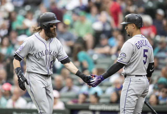 Colorado Rockies' Charlie Blackmon, left, is congratulated by Carlos Gonzalez after hitting a solo home run off of Seattle Mariners starting pitcher Felix Hernandez during the first inning of a baseball game, Friday, July 6, 2018, in Seattle. (AP Photo/Stephen Brashear)