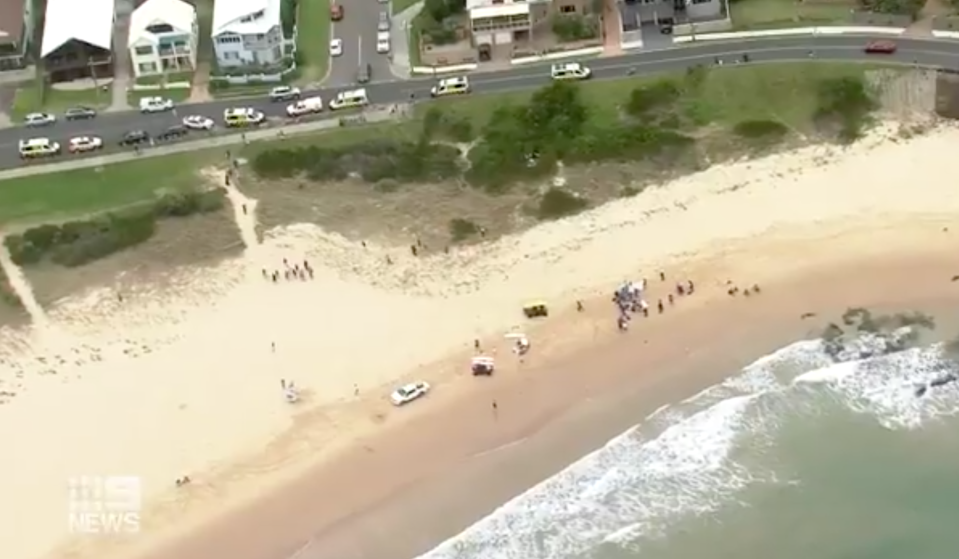 Paramedics and police at Woonona Beach after a man died following two children being swept into the sea.