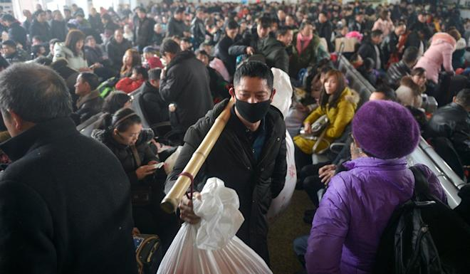 A man carries his belongings as he walks among passengers on the first day of the annual Spring Festival travel rush in 2019. Photo: Reuters