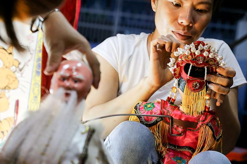 The puppets need to be prepared before the start of the Teochew puppet show.
