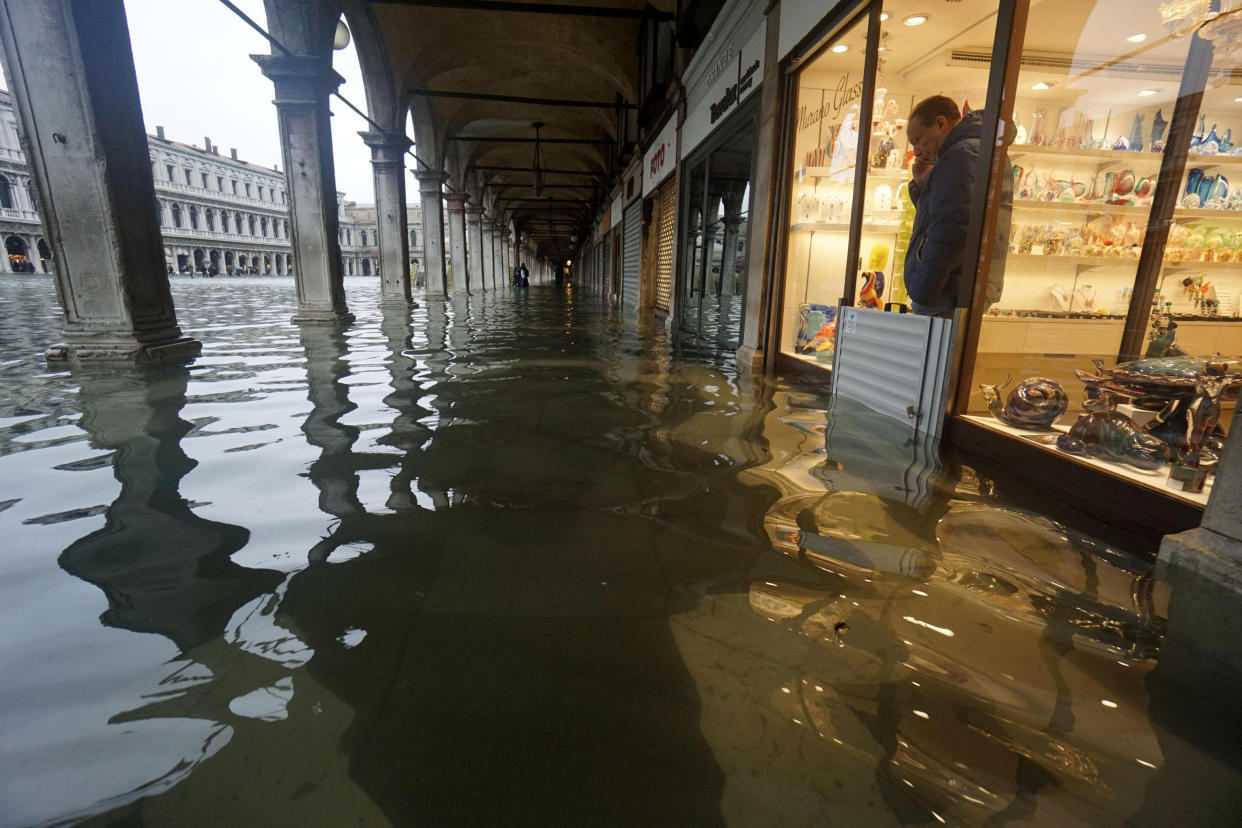 A shopkeeper looks out of his shop at a flooded St. Mark's Square on the occasion of a high tide, in Venice, Italy, Tuesday, Nov. 12, 2019. (Photo: Andrea Merola/ANSA via AP)