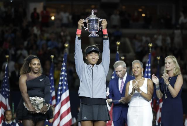 FILE - In this Sept. 8, 2018, file photo, Naomi Osaka, of Japan, holds the trophy after defeating Serena Williams in the women's final of the U.S. Open tennis tournament, in New York. Caroline Wozniacki will be defending a Slam title for the first time after winning in Melbourne a year ago, while Naomi Osaka will enter a major tournament with the label major champion for the first time after taking home the trophy at the U.S. Open in September.(AP Photo/Julio Cortez, File)