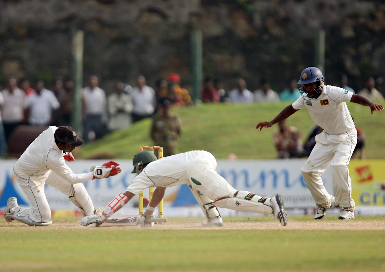 GALLE, SRI LANKA - JUNE 25:  Pakistan batsman Adnan Akmal (C) successfully dives to avoid being run out as Sri Lankan's wicketkeeper Prasanna Jayawardene (L) attempts to breaks to stumps during day four of the first test between Sri Lanka and Pakistan at Galle International Stadium on June 25, 2012 in Galle, Sri Lanka.  (Photo by Buddhika Weerasinghe/Getty Images)