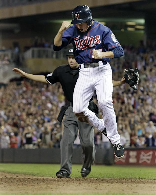 Minnesota Twins' Doug Bernier leaps for joy as he scores the winning run on a walkoff single by Chris Herrmann off Chicago White Sox pitcher Ramon Troncoso in a baseball game, Thursday, Aug. 15, 2013 in Minneapolis. The Twins won 4-3. (AP Photo/Jim Mone)