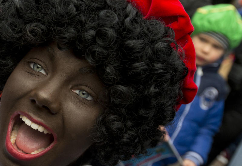 "In this Saturday, Nov. 12, 2016 file photo, a Black Pete interacts with children during the arrival of Sinterklaas in Maassluis, Netherlands, Saturday, Nov. 12, 2016. Saturday, Nov. 12, 2016. A court in the Netherlands has convicted 34 people on Friday NOv. 9, 2018, who blocked a highway last year to prevent anti-racism demonstrators reaching the nationally televised arrival of Sinterklaas, the Dutch version of Santa Claus, and his helpers called ""Zwarte Piet"", or Black Petes. Black Pete is often played by white people with their faces daubed in dark makeup. (AP Photo/Peter Dejong)"