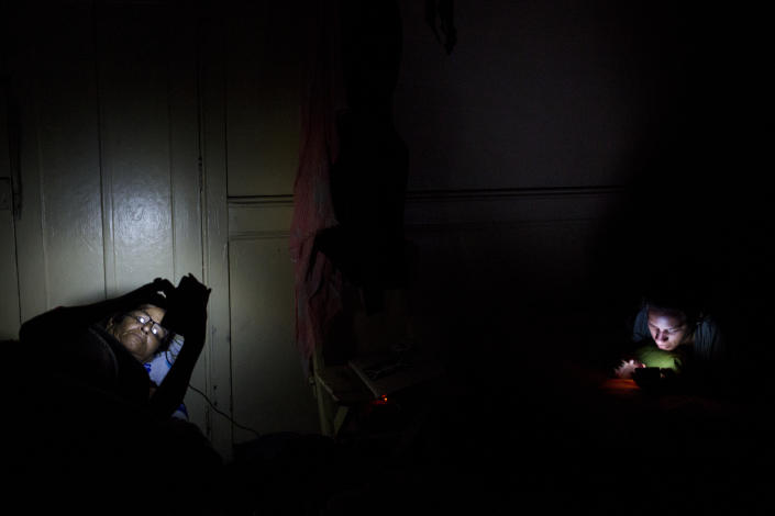 May 23, 2016 - Marta and Liset (right) check their phones after arriving in Lima before dawn. (Photo: Lisette Poole)