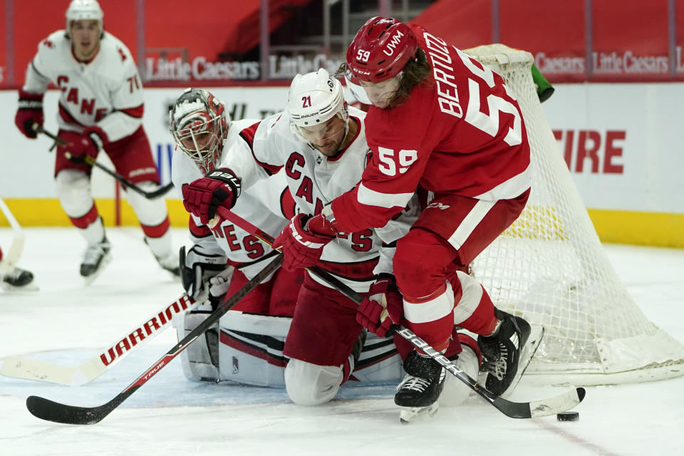 Carolina Hurricanes right wing Nino Niederreiter (21) defends Detroit Red Wings left wing Tyler Bertuzzi (59) in front of goaltender Petr Mrazek (34)in the second period of an NHL hockey game Saturday, Jan. 16, 2021, in Detroit. (AP Photo/Paul Sancya)