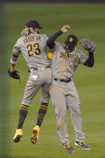 San Diego Padres' Fernando Tatis Jr., left, and Trent Grisham celebrate after the Padres defeated the Los Angeles Dodgers 6-2 in a baseball game Tuesday, Aug. 11, 2020, in Los Angeles. (AP Photo/Mark J. Terrill)