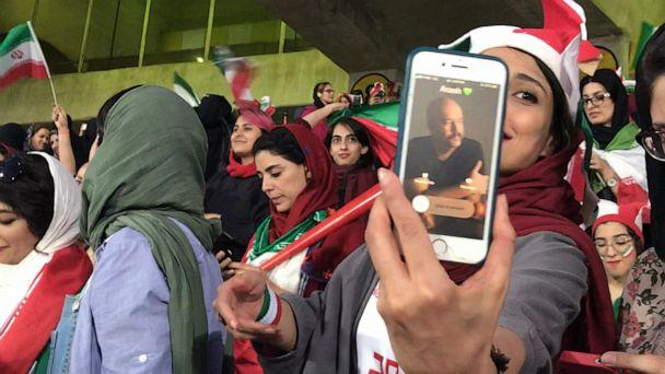 PHOTO: Zahra Ahooei receives a phone call from her husband during half time while attending a soccer game in Tehran, Iran, Oct. 10, 2019. They could not sit besides each other because men and women sections are segregated. (Somaye Malekian/ABC News)