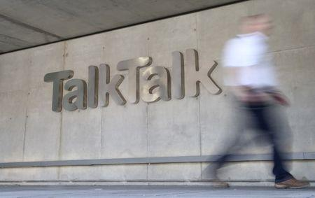 A man passes a branded logo outside the Talktalk headquarters in London