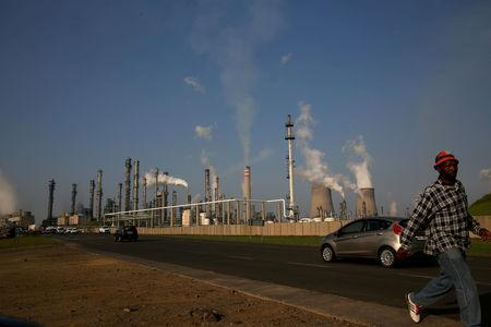 FILE PHOTO: A man walks past South African petrochemical company Sasol's synthetic fuel plant in Secunda