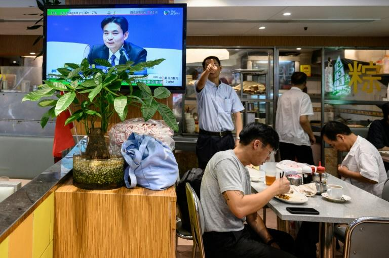 "A Hong Kong restaurant worker (background C) gestures in reaction to a live television broadcast showing Beijing official Yang Guang, who said ""radical protests"" pushed Hong Kong to ""a dangerous abyss"""