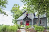 <p>Painting the window frames to match the splash of color on the front door really ties this tucked-away house together. </p>