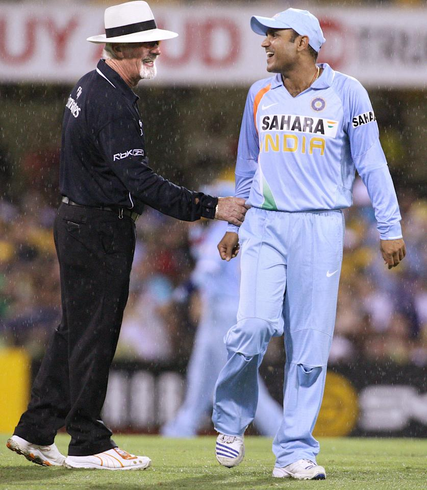 Indian fieldsman Virender Sehwag (R) enjoys a lighter moment with umpire Rudi Koertzen (L) during their match against Australia being played at the Gabba in Brisbane, 03 February 2008.  Australia is chasing India's score of 194 from their 45 overs in the rain-affected match.    RESTRICTED TO EDITORIAL USE PUSH TO MOBILE SERVICES OUT.      AFP PHOTO/William WEST (Photo credit should read WILLIAM WEST/AFP/Getty Images)