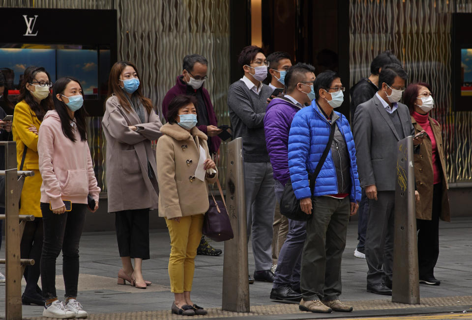 People wear masks on a downtown street corner in Hong Kong, Tuesday, Feb. 4, 2020. Hong Kong on Tuesday reported its first death from a new virus, a man who had traveled from the mainland city of Wuhan that has been the epicenter of the outbreak. (AP Photo/Vincent Yu)