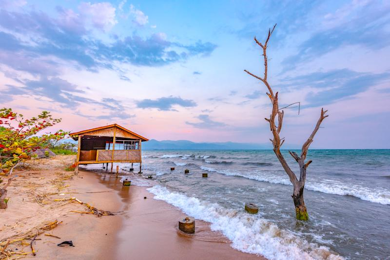 Burundi Bujumbura lake Tanganyika, windy cloudy sky and sand beach at sea lake in East Africa, Burundi sunset with house from wood and dead tree in the sea
