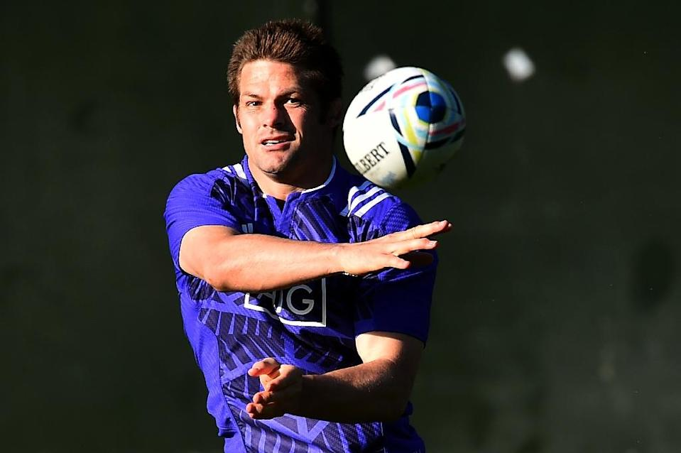 New Zealand All Blacks' flanker and captain Richie McCaw passes the ball during a training session in Cardiff, south Wales, on September 28, 2015, during the Rugby World Cup (AFP Photo/Gabriel Bouys)