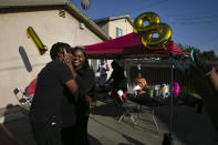 Kyaira Shaw gets a kiss from her boyfriend, Camari Baseer, left, while posing for photos at her 18th birthday party in the Watts neighborhood of Los Angeles, Wednesday, June 17, 2020. (AP Photo/Jae C. Hong)