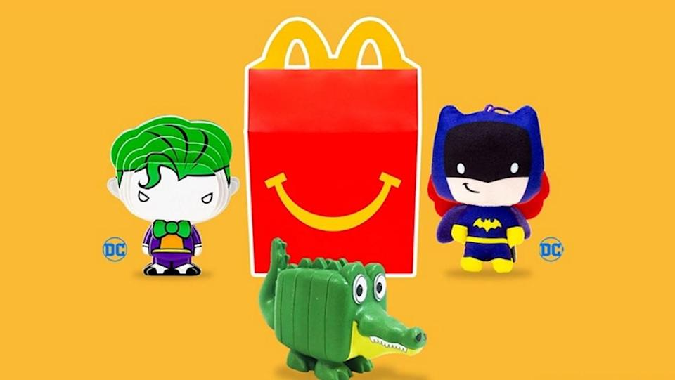 A Happy Meal Box surrounded by three toys, a Joker, Bat Girl, and alligator. These Mcdonald's Happy Meal toys are designed in sustainable ways.