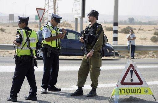 Israeli police and a soldier guard a checkpoint as they look for militants who infiltrated the Egyptian border in June