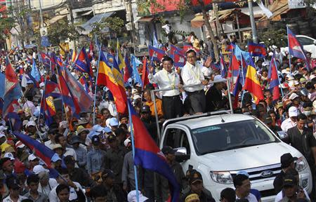 Sam Rainsy (center, R), president of the opposition Cambodian National Rescue Party (CNRP) and party vice-president Kem Sokha (center, L), stand on a vehicle while greeting supporters during a protest in Phnom Penh December 29, 2013. REUTERS/Stringer