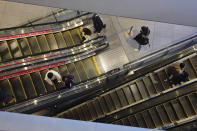 People wearing protective masks to help curb the spread of the coronavirus take usually crowded escalators at a shopping arcade in Tokyo Saturday, Jan. 9, 2021. The Japanese capital confirmed more than 2200 new coronavirus cases on Saturday. Japanese Prime Minister Yoshihide Suga declared a state of emergency last Thursday for Tokyo and three other prefectures to ramp up defenses against the spread of the coronavirus. (AP Photo/Eugene Hoshiko)