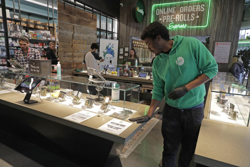 In this photo taken March 24, 2020, budtender Matt Anderson wears gloves as he wipes down a counter at The Reef Capitol Hill, a marijuana store in Seattle. Earlier in the week, Washington Gov. Jay Inslee ordered nonessential businesses to close and the state's more than 7 million residents to stay home in order to slow the spread of the new coronavirus. In Washington and several other states where marijuana is legal, pot shops and workers in the market's supply chain were deemed essential and allowed to remain open. Signs posted at the store said that The Reef is donating 5% of its profits to Seattle-area coronavirus relief efforts. (AP Photo/Ted S. Warren)