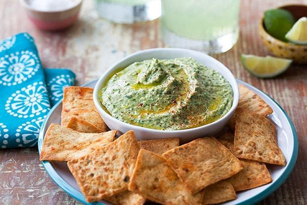 """This hummus recipe has all kinds of upgrades, including tomatillos, poblano peppers, Anaheim peppers, white onion, garlic, lime juice, cilantro, and creamy avocado. Served with pita chips or a vegetable tray, it makes for one awesome appetizer. <a href=""""https://www.epicurious.com/recipes/food/views/chile-verde-hummus-56389853?mbid=synd_yahoo_rss"""" rel=""""nofollow noopener"""" target=""""_blank"""" data-ylk=""""slk:See recipe."""" class=""""link rapid-noclick-resp"""">See recipe.</a>"""