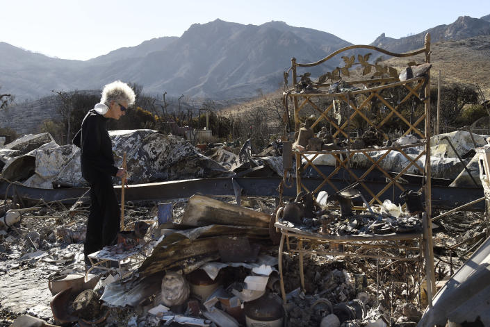<p>Marsha Maus, who has lived in the Seminole Springs Mobile Home Park for 15 years, looks through her charred belongings onNov. 11, 2018, after wildfires tore through her neighborhood in Agoura Hills, Calif. (Photo: Chris Pizzello/AP) </p>