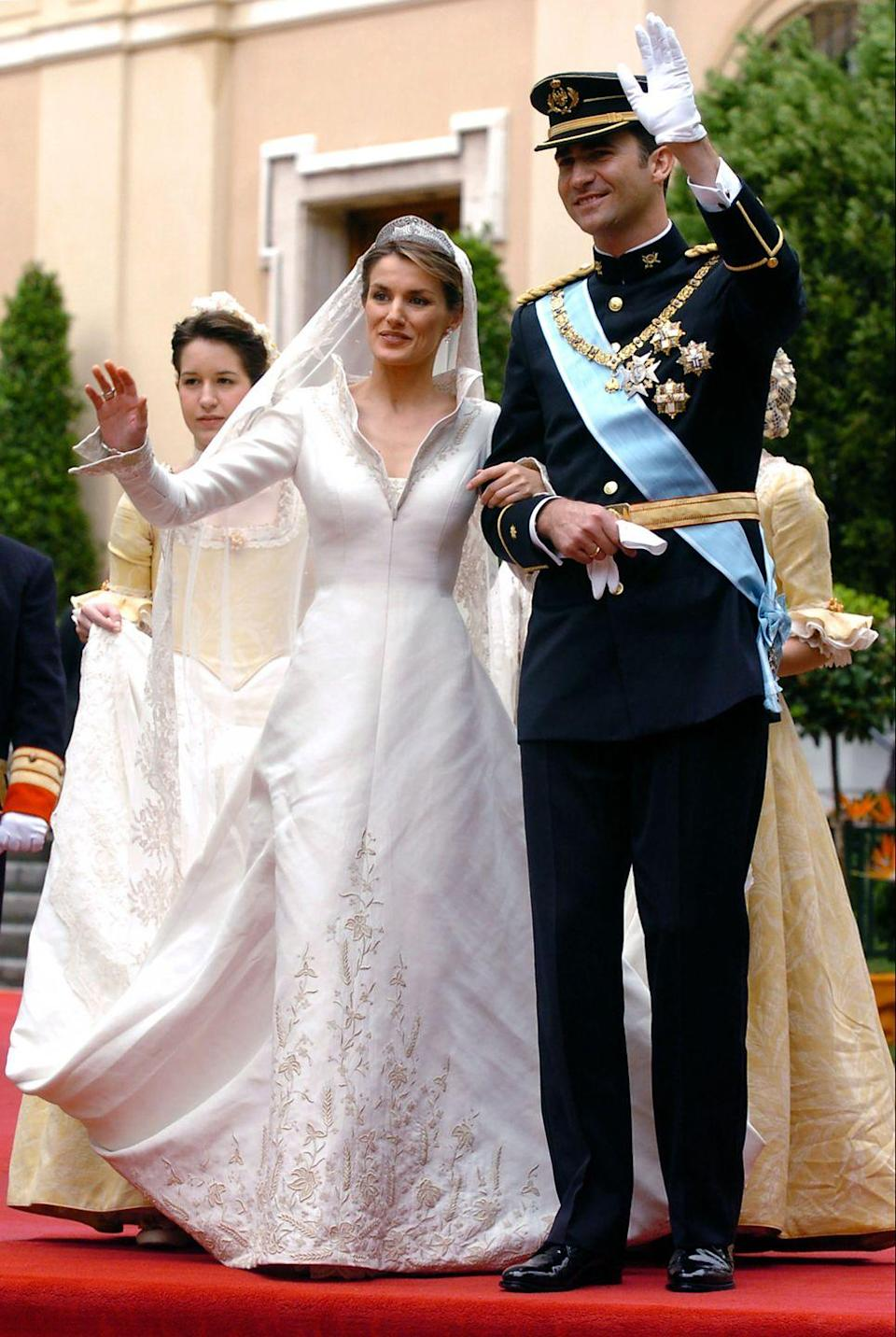 <p>Couturier Manuel Pertegaz designed the journalist-turned-queen's silk-woven, open-collar dress, which featured a 15-foot train embroidered in silk and gold. </p>