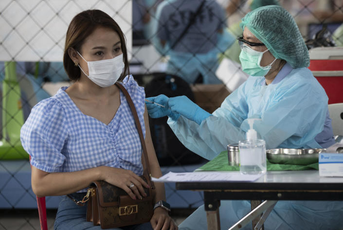 A health worker administers a dose of the Sinovac COVID-19 vaccine to a person working at an entertainment venue where a new cluster of COVID-19 infections was found, in Bangkok, Thailand, Wednesday, April 7, 2021. (AP Photo/Sakchai Lalit)