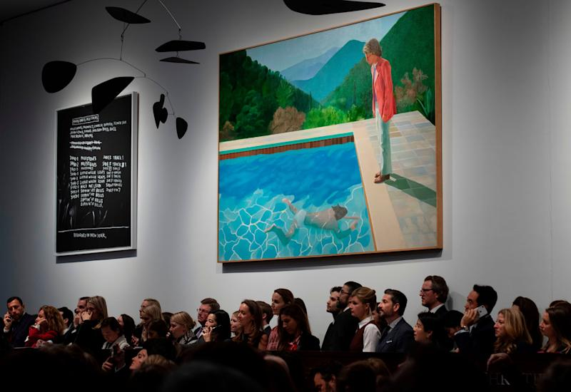 A crowd of people attend the Post-War and Contemporary Art Evening Sale where David Hockney's Portrait of an Artist (Pool with Two Figures)is displayed at Christie's in New York November 15, 2018. - David Hockneys Famed Pool Scene Sells for $90.3 M. at Christies, New Record for Work by Living Artist at Auction. (Photo by Don EMMERT / AFP) (Photo credit should read DON EMMERT/AFP/Getty Images)