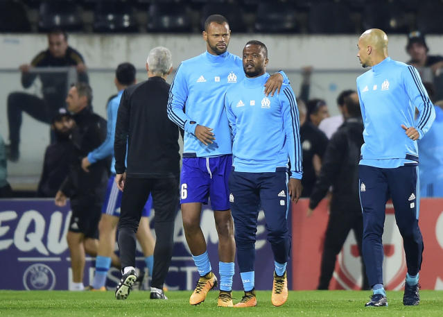 Bad blood: Marseille's Patrice Evra, centre right, attacking one of his club's own fans last night