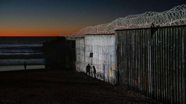 PHOTO: The sun sets while people walk close to the border fence between the U.S. side of San Diego, Calif., and Tijuana, in Mexico, Jan. 2, 2019. (Daniel Ochoa de Olza/AP)