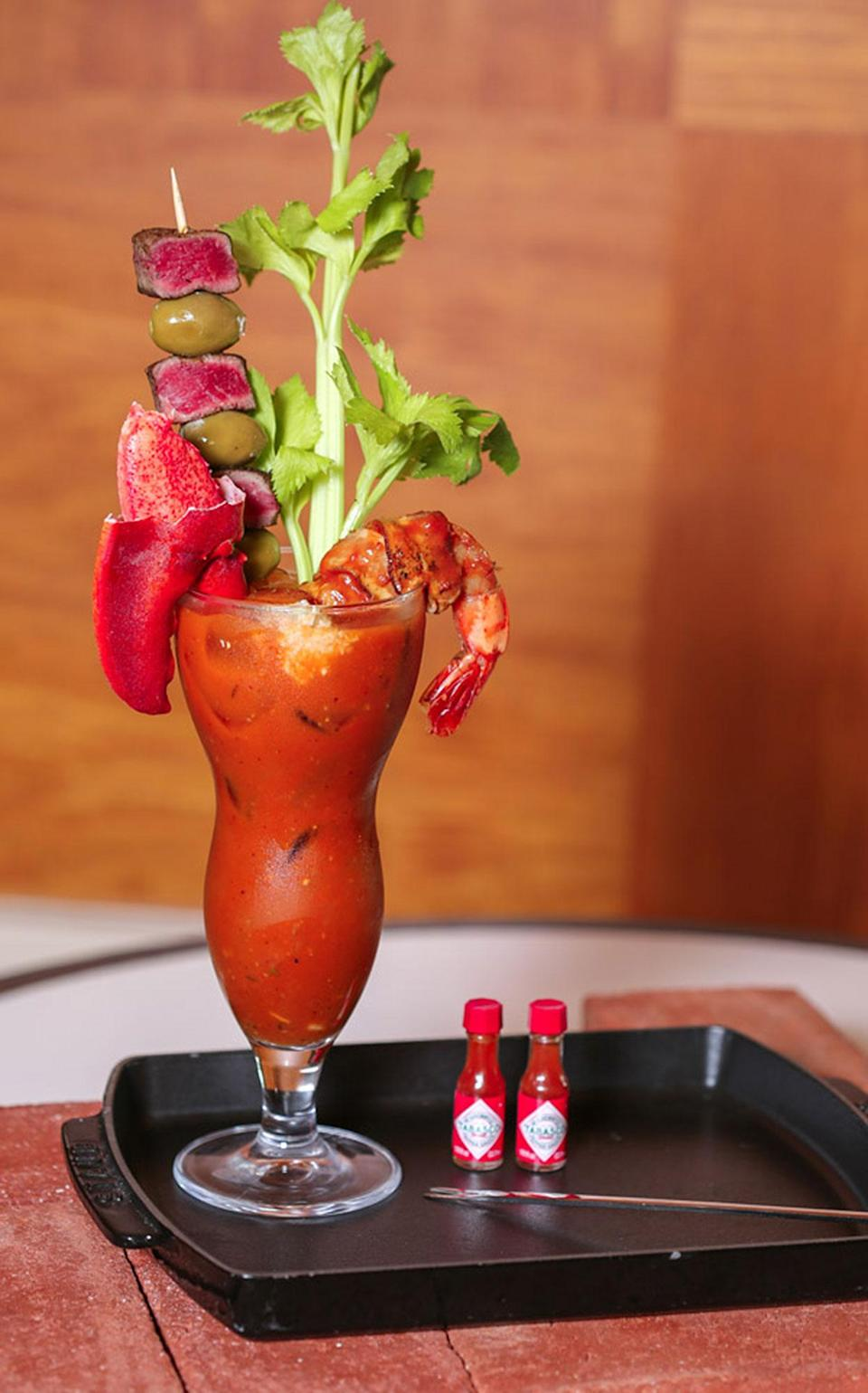 """<p><strong>Where to Get It: </strong>Phin's Bar at the Walt Disney World Swan and Dolphin Resort ($27-30) <strong>Lou's Review: """"</strong>This elegant-looking bar is where you need to go on Sundays between 10 a.m. and 2 p.m. You can order from a selection of 4 """"Proud Marys"""", crafted by the chefs of their signature restaurants (some of the best of the best in Walt Disney World, by the way.) The <strong>Zoo Mary </strong>is Todd English's take on a traditional Bloody Mary, with old bay seasoning, crab louie, tender lobster tail, and a ginormous cocktail shrimp. The <strong>Maria Italiana</strong> is their Il Mulino Trattoria-inspired version, with giardiniera, Italian seasoning, and has <em>4</em> giant antipasti skewers. Like sushi? The subtly spicy <strong>Dragon Mary</strong> is inspired by the sushi chefs at Kimonos, and contains yuzu juice, sriracha, and a dragon roll skewer. And finally, my favorite of the four is their Don Shula's-inspired <strong>Hail Mary</strong> (pictured) includes tender cubes of with filet mignon, lobster claw, BBQ shrimp, and steak sauce. (Note: These are also all available as non-alcoholic options.)""""</p>"""