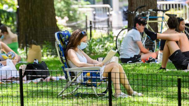 PHOTO: A person wears a protective face mask while reading a book in Washington Square Park as New York City moves into Phase 3 of re-opening following restrictions imposed to curb the coronavirus pandemic on July 12, 2020. (Noam Galai/Getty Images)