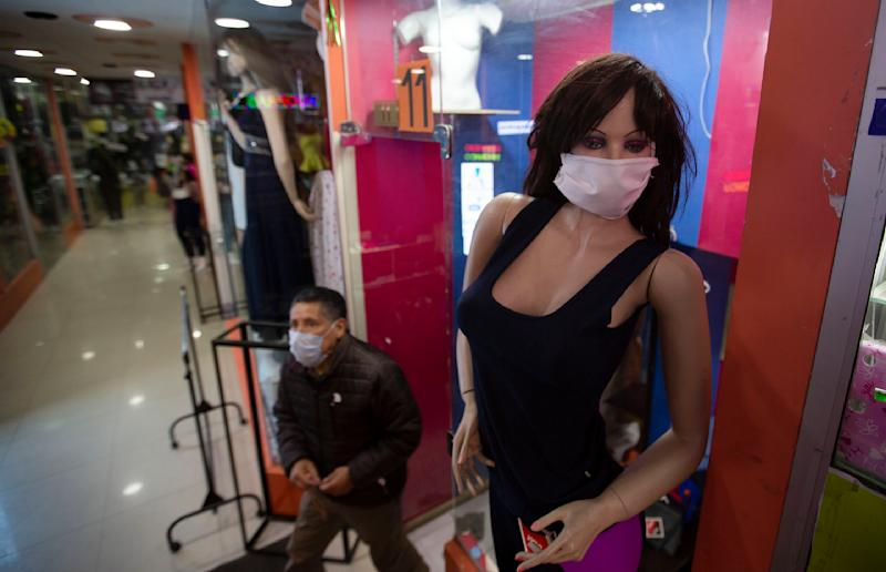 A mannequin wearing a face mask stands at the entrance of a women's clothing store in La Paz, Bolivia, Monday, June 1, 2020. After more than two months of quarantine to curb the spread of the new coronavirus the government authorized the restart of public transport and several industrial and commercial activities. (AP Photo/Juan Karita)