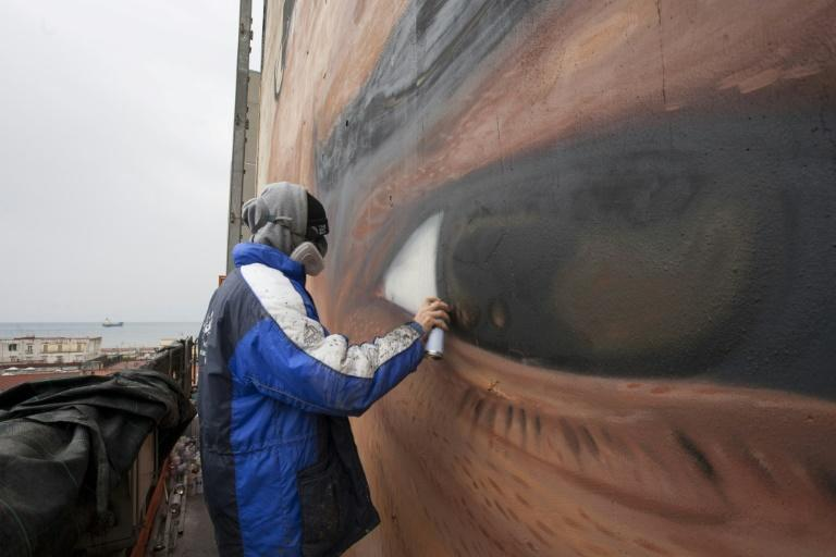 Italian artist Jorit Agoch works on a mural representing football superstar Diego Armando Maradona