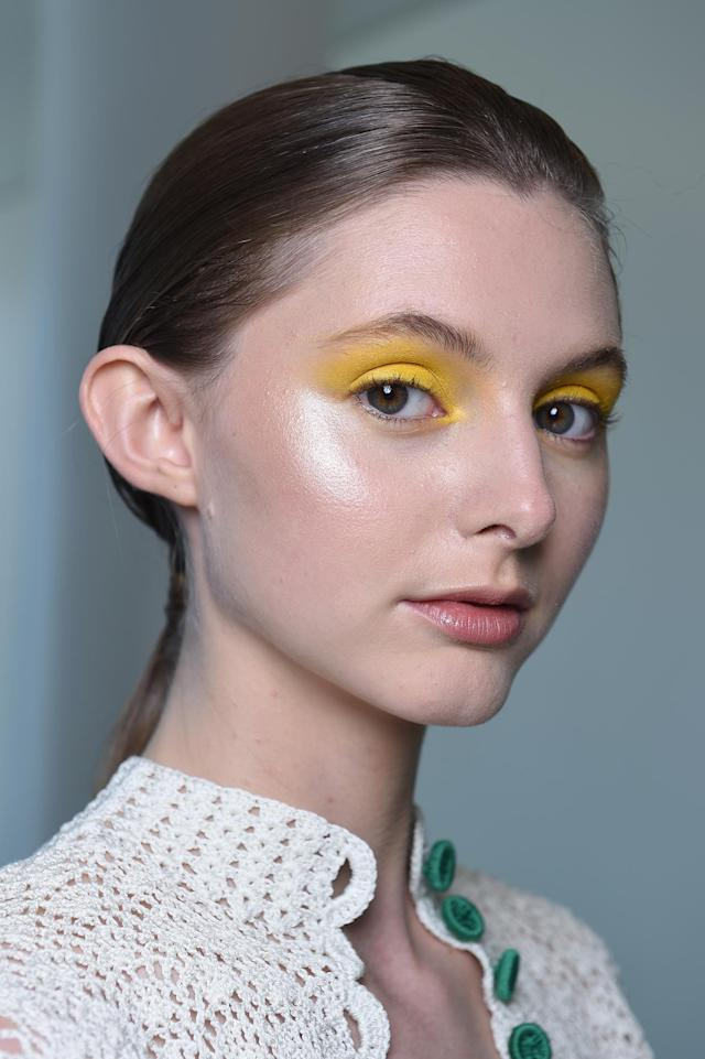 <p>A model wears bright yellow eyeshadow and a touch of cheek highlighter. (Photo: NARS) </p>