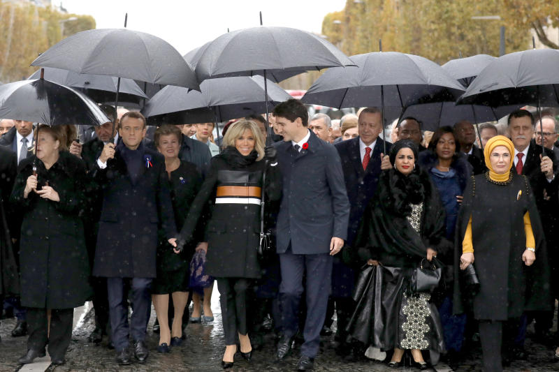 French President Emmanuel Macron's wife, Brigitte Macron (center left) listens to Canadian Prime Minister Justin Trudeau (center right) as they walk with world leaders toward the Arc de Triomphe in Paris on Sunday. (THE ASSOCIATED PRESS)