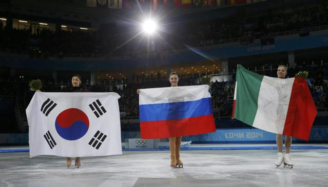 Russia's Adelina Sotnikova (C), Korea's Yuna Kim (L) and Italy's Carolina Kostner celebrate with their flags after the flower ceremony during the Figure Skating Women's free skating Program at the Sochi 2014 Winter Olympics, February 20, 2014. REUTERS/Alexander Demianchuk (RUSSIA - Tags: OLYMPICS SPORT FIGURE SKATING)