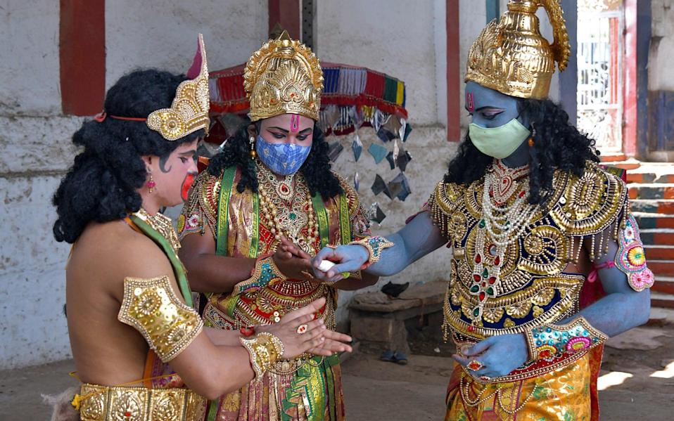 Men dressed as Hindu deities from the epic Ramayan sanitise their hands before going on a public awareness campaign against the spread of Covid-19, on the occasion of the Hindu festival 'Ram Navami', in Bangalore - AFP via Getty