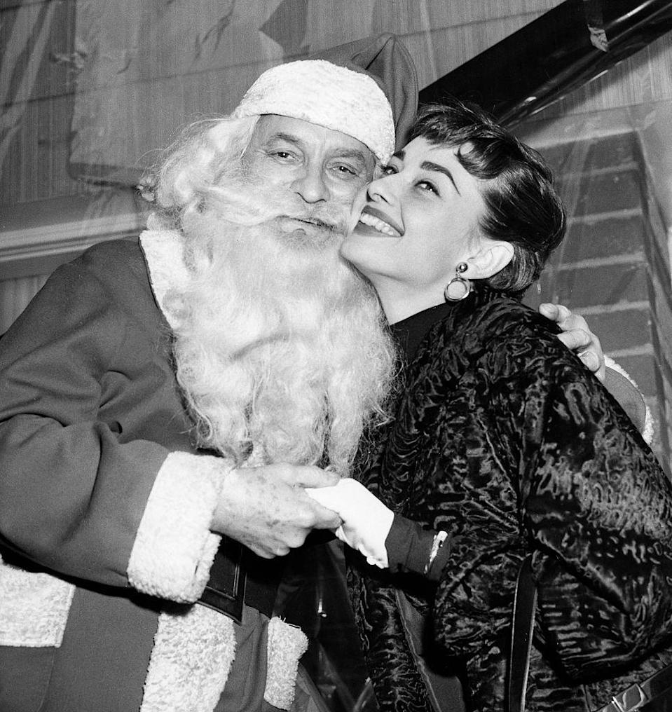 <p>Audrey Hepburn flashes a wide grin as she poses with Santa while at a charity event in New York City during the holidays. </p>