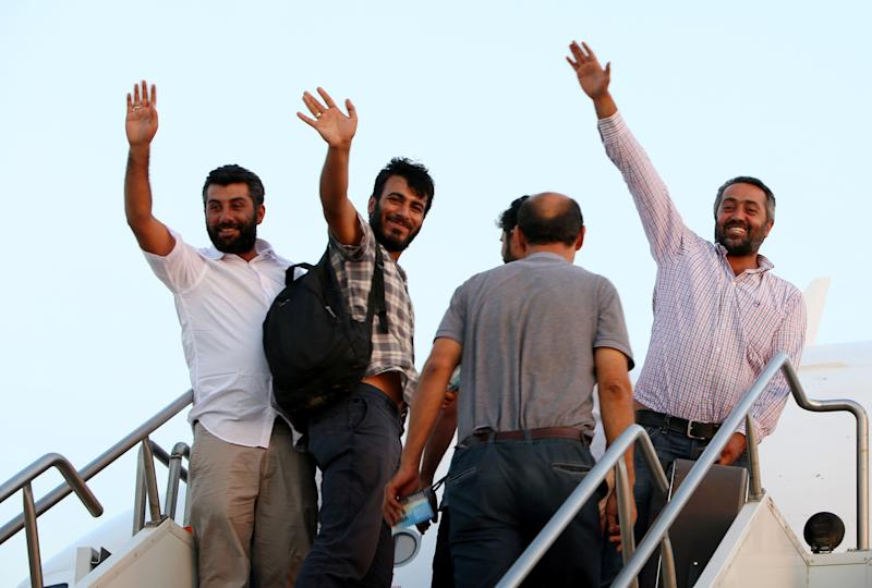Some of the thirty-two Turkish truck drivers, held hostage for three weeks by Islamic militants in Iraq, wave as they board an aircraft n July 3, 2014 at Arbil's airport (AFP Photo/Safin Hamed)