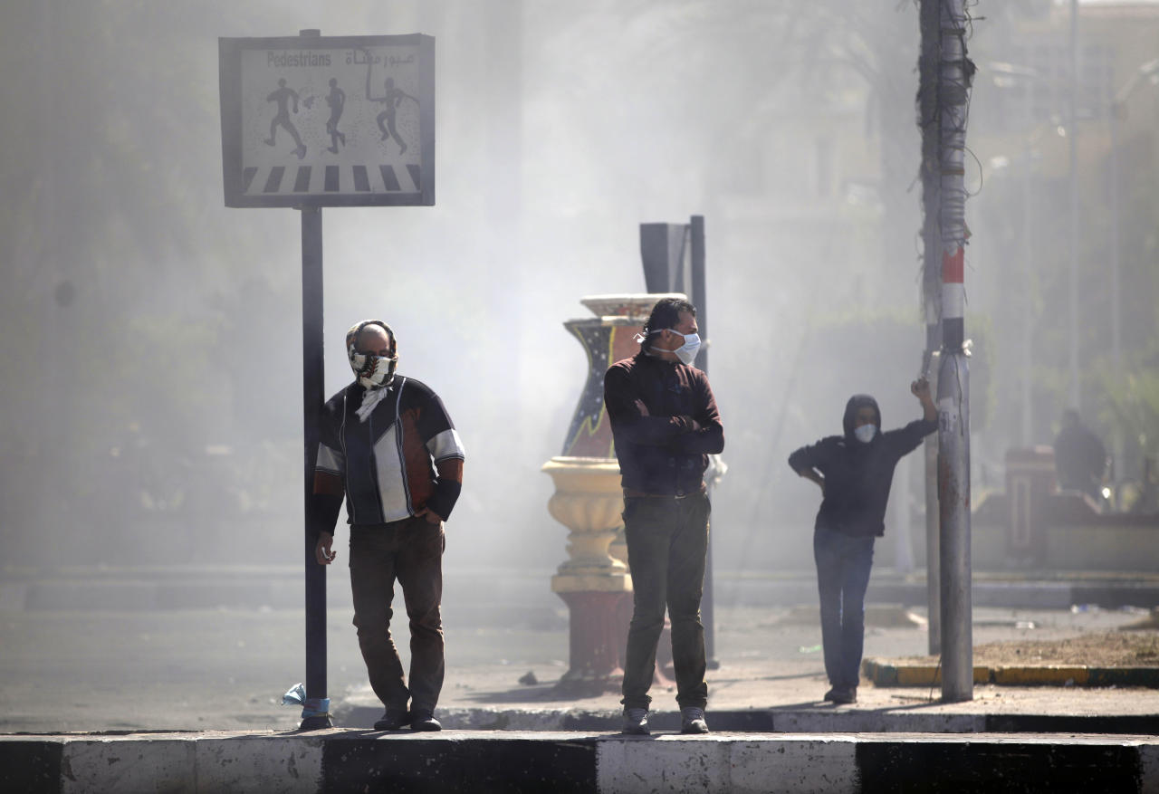 Egyptians cover their faces from tear gas during clashes between protesters and riot police near the state security building in Port Said, Egypt, Wednesday, March 6, 2013. Clashes between protesters and police have broken out in this restive Egyptian port city despite efforts by the military to separate the two sides. (AP Photo/Khalil Hamra)